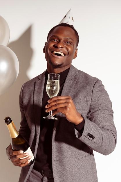 Glücklicher mann, der ein glas champagner hält Kostenlose Fotos