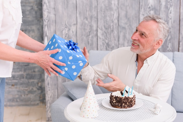 Glücklicher mann, der geburtstagsgeschenk von seiner frau nahe kuchen und partyhut auf tabelle empfängt Kostenlose Fotos