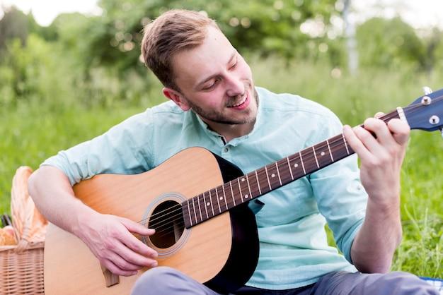 Glücklicher mann, der gitarre spielt Kostenlose Fotos