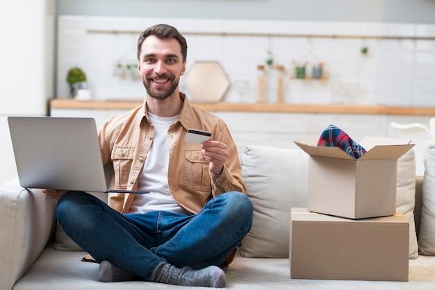 Glücklicher mann, der laptop und kreditkarte hält Kostenlose Fotos
