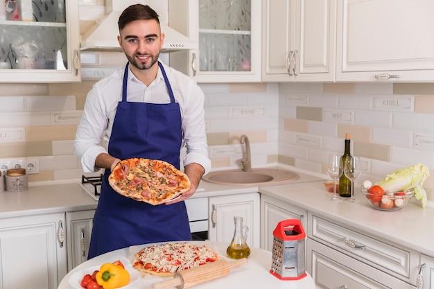 Glücklicher mann, der mit pizzas in der küche steht Kostenlose Fotos