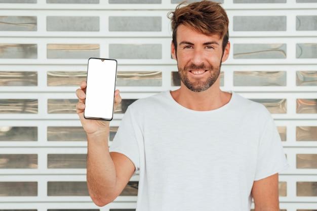 Glücklicher mann, der mobiltelefon mit modell hält Kostenlose Fotos