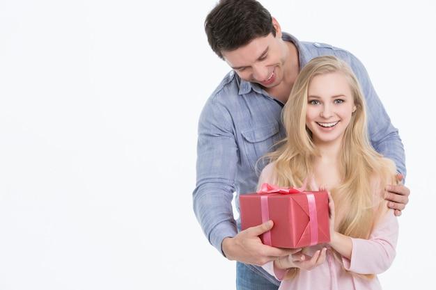 Glücklicher mann, der seiner freundin ein geschenk gibt. urlaub Premium Fotos