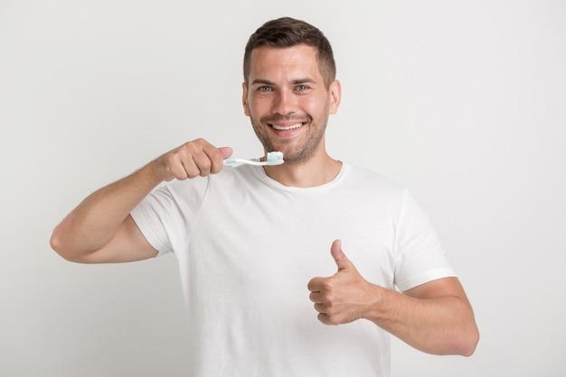 Glücklicher mann, der sich daumen zeigt und zahnbürste mit paste hält Kostenlose Fotos