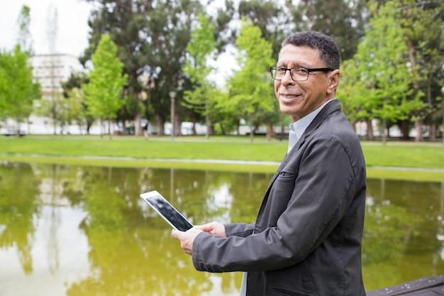 Glücklicher mann, der tablette verwendet und im stadtpark steht Kostenlose Fotos