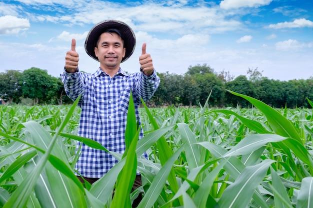 Glücklicher mann des porträts ist lächelnder daumen, der oben kamera am maisbauernhof betrachtet Premium Fotos