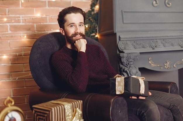 Glücklicher mann im roten pullover. mann vor dem kamin. männchen auf dem hintergrund des weihnachtsbaumes. Kostenlose Fotos