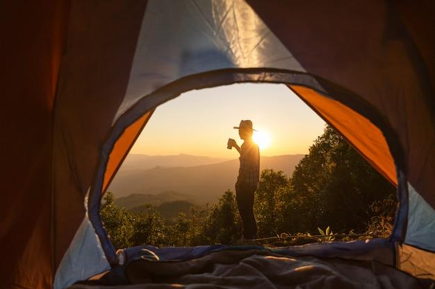 Glücklicher mann mit dem halten der kaffeetasse in der nähe von zelt um berge zu bleiben Kostenlose Fotos