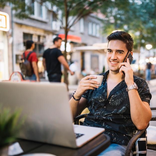 Glücklicher mann mit dem tasse kaffee sprechend auf mobiltelefon Kostenlose Fotos