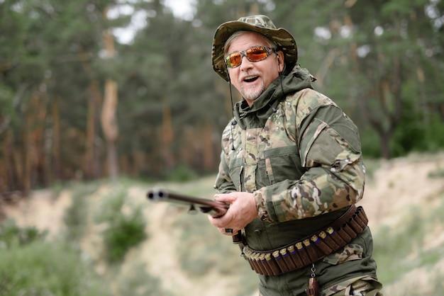 Glücklicher mann mit der schrotflinte, die tätigkeit im freien jagt. Premium Fotos