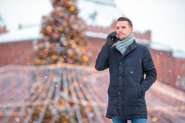 Glücklicher mann nahe tannenbaumast im schnee für neues jahr. Premium Fotos