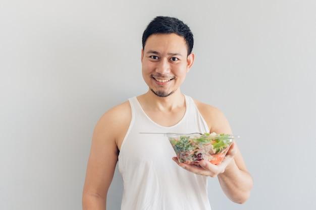 Glücklicher mann stellt gesunde salatmahlzeit dar. Premium Fotos