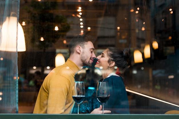 Glücklicher mann und frau nahe gläsern wein im restaurant Kostenlose Fotos