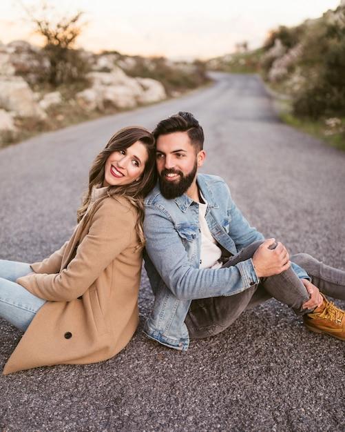 Glücklicher mann und frau sitzen auf der straße Kostenlose Fotos