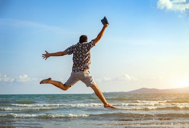 Glücklicher mannfreiheitsprungsozeanmeer-scape hintergrund Premium Fotos