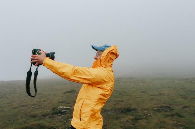 Glücklicher netter mann, der selfie am windigen tag mit nebel nimmt Premium Fotos
