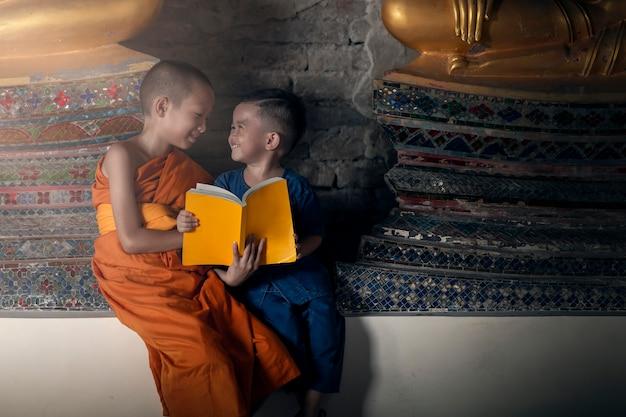 Glücklicher novizenmönch unterrichtet glückliche kleine kinder im tempel mit spaß am inhalt des dharma. atutthaya thailand Premium Fotos