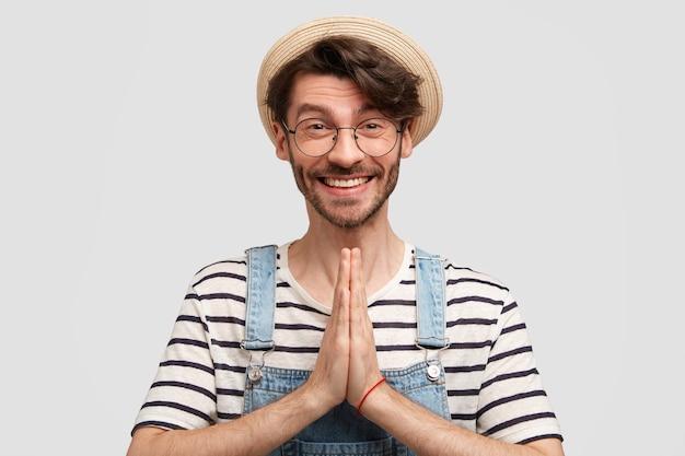 Glücklicher optimistischer männlicher bauer in lässigem outfit und strohhut, hat positives lächeln, hält hände in gebetsgeste, bittet um etwas wünschenswertes, isoliert über weißer wand. menschen- und glaubenskonzept Kostenlose Fotos