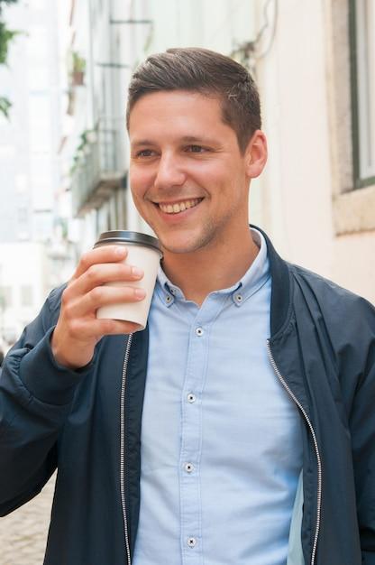 Glücklicher positiver student, der mitnehmerkaffee trinkt Kostenlose Fotos