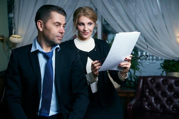 Glücklicher reifer geschäftsmann und geschäftsfrau, die mit dokumenten arbeiten Premium Fotos