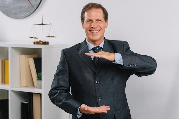 Glücklicher reifer männlicher rechtsanwalt, der handrahmen macht Kostenlose Fotos