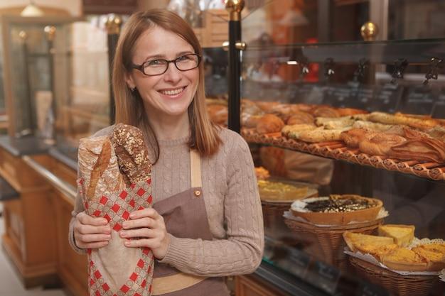 Glücklicher reifer weiblicher bäcker, der nach vorne lächelt und laib des frischen brotes hält Premium Fotos