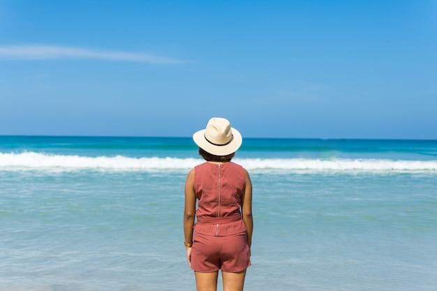 Glücklicher reisefrauenstand auf sand des meeres mit blauem himmel am sonnigen tag. Premium Fotos