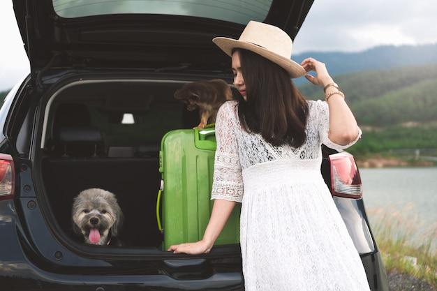 Glücklicher reisender der jungen frau, der im fließheckauto mit hunden sitzt. Premium Fotos
