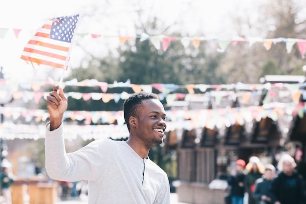 Glücklicher schwarzer mann, der amerikanische flagge wellenartig bewegt Kostenlose Fotos