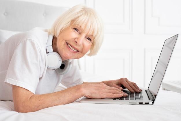 Glücklicher senior mit kopfhörern und laptop Kostenlose Fotos