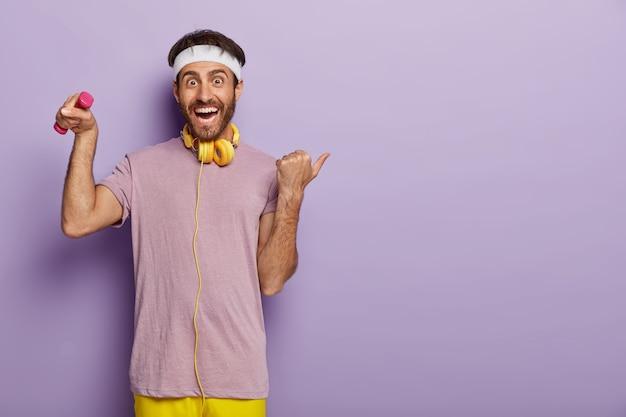 Glücklicher sportler hebt arm mit hantel, hat sporttraining drinnen, trägt stirnband und lässiges violettes t-shirt, hört musik in kopfhörern während des trainings, zeigt mit dem daumen weg auf den kopierplatz rechts Kostenlose Fotos