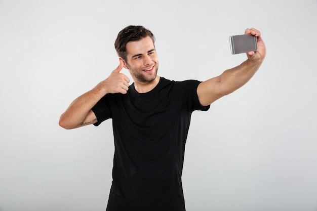 Glücklicher sportler machen selfie per handy. Kostenlose Fotos