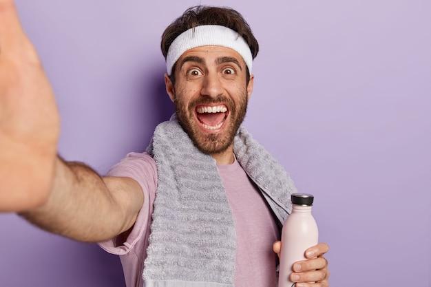 Glücklicher sportler streckt die hand aus und macht selfie während des trainings, hält wasserflasche, bleibt hydratisiert und gesund, trägt handtuch am hals isoliert auf lila wand Kostenlose Fotos