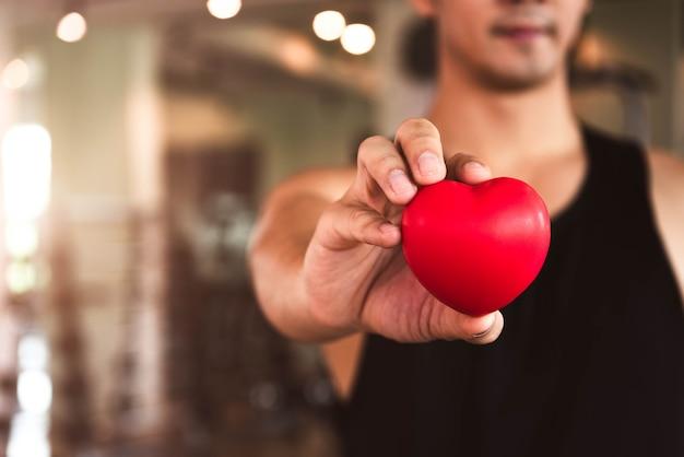Glücklicher sportmann, der rotes herz im eignungsturnhallenclub hält. medizinischer herz-kreislauf-lebensstil. Premium Fotos