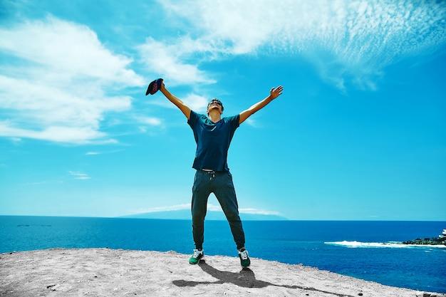 Glücklicher stilvoller mann in der freizeitkleidung, die auf der klippe des berges steht Kostenlose Fotos