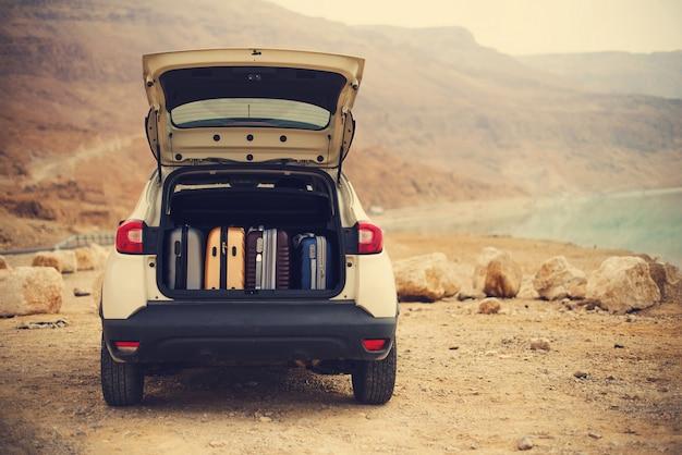 Glücklicher stilvoller reisender der jungen frau auf der strandstraße, die auf weißem kreuzauto sitzt Premium Fotos