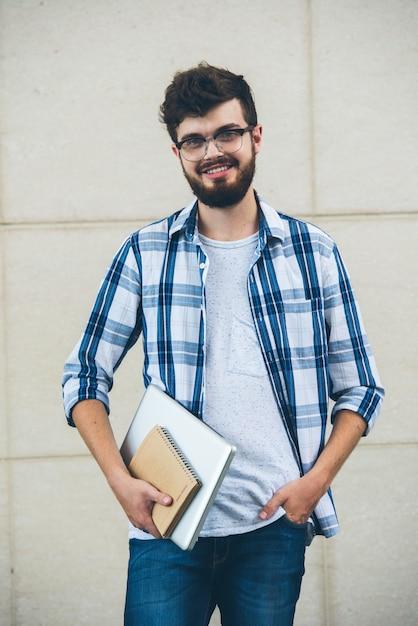 Glücklicher student, der auf der kamera draußen hält texrbooks aufwirft Kostenlose Fotos