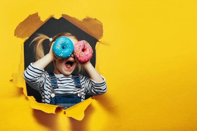 Glücklicher süßer junge hat spaß, der mit donuts auf schwarzer hintergrundwand gespielt wird. Premium Fotos
