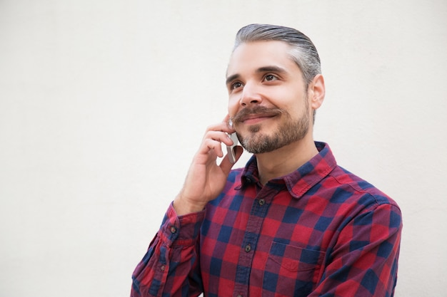 Glücklicher träumerischer mann, der am telefon spricht Kostenlose Fotos
