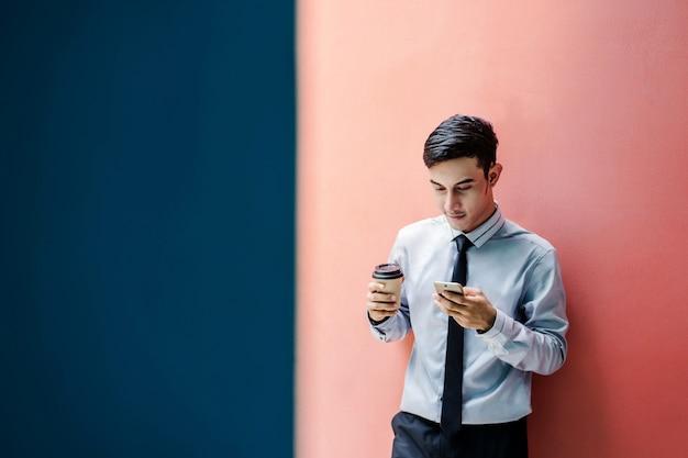 Glücklicher und freundlicher junger attraktiver geschäftsmann benutzen ein intelligentes telefon an der bunten wand Premium Fotos