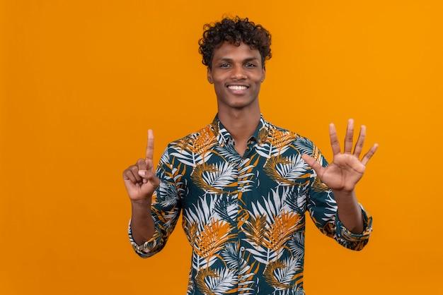 Glücklicher und lächelnder junger gutaussehender dunkelhäutiger mann mit lockigem haar im hemd mit blattdruck, während er mit den fingern nummer sechs zeigt Kostenlose Fotos