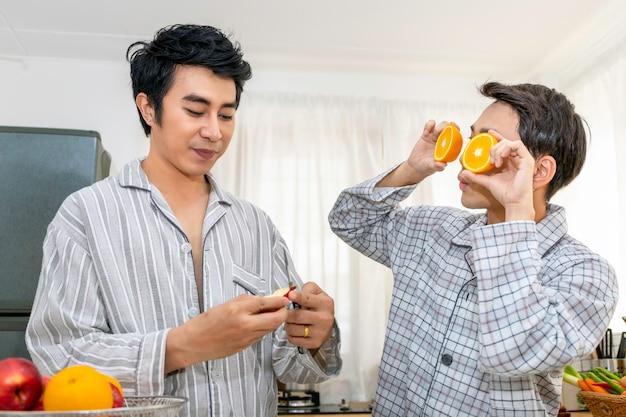 Glücklicher und lustiger kochender salat der asiatischen homosexuellen paare an der küche. konzept lgbt-homosexuell. Premium Fotos