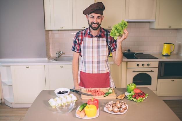 Glücklicher und positiver chef steht in der küche und schaut. er lächelt. junger mann hält letuce in der hand. er trägt pron. es gibt eier und gemüse am tisch. Premium Fotos