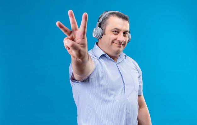 Glücklicher und positiver mann mittleren alters im blau gestreiften hemd im kopfhörer, der mit den fingern nummer sechs auf einem blauen raum zeigt Kostenlose Fotos