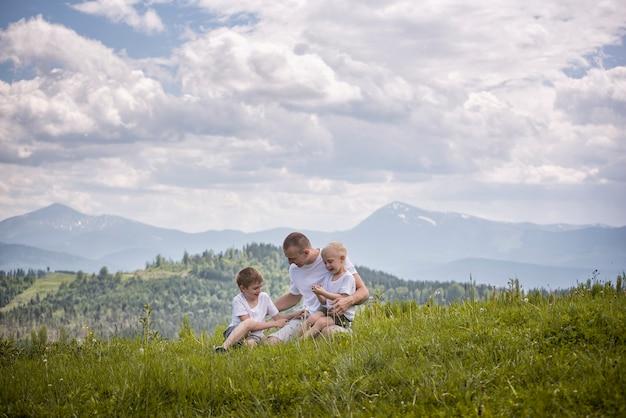 Glücklicher vater mit seinen zwei jungen söhnen, die auf dem gras sitzen Premium Fotos