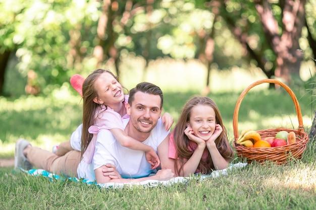 Glücklicher vater und kleine töchter entspannen sich am see Premium Fotos