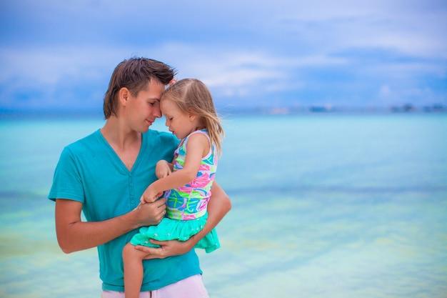 Glücklicher vater und seine entzückende kleine tochter am weißen sandigen strand Premium Fotos