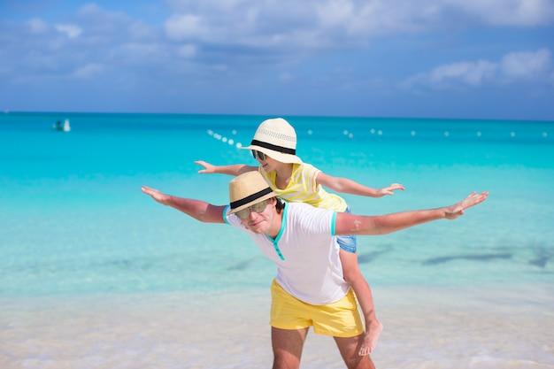 Glücklicher vater und seine entzückende kleine tochter haben spaß am tropischen strand Premium Fotos