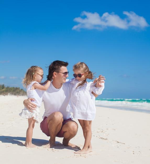 Glücklicher vater und seine entzückenden kleinen töchter am sonnigen tag Premium Fotos