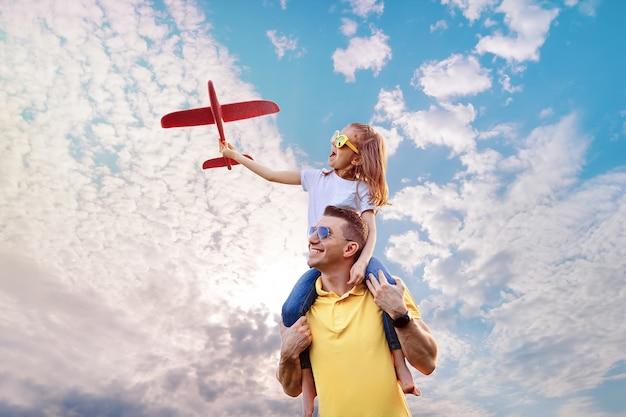 Glücklicher vater und tochter spielen mit flugzeug Premium Fotos